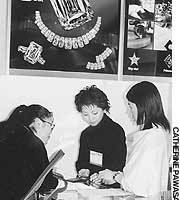 Shop clerks talk with a visitor to the International Jewelry Tokyo trade show in January.