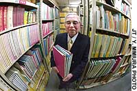 Personal Data Library President Takeo Tamura stands among shelves of files at his office in Tokyo's Shinbashi district.