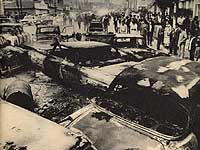People stand by the burned vehicles of U.S. service personnel the morning after the Koza riot of Dec. 20, 1970.