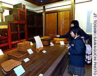 Michiko Abe (foreground) and Erika Tsuda, from Watanoha Junior High School in Ishinomaki, Miyagi Prefecture, examine items on display at the Furniture Museum.