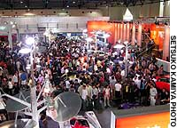 Visitors mill around cars displayed at the Beijing Motor Show in June.