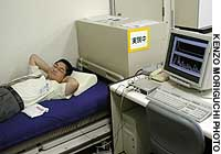 An employee at Sanyo Electric Co. in Osaka lies on a bed to demonstrate a newly developed sensor, which is under his waist, that measures heartbeat and breathing.