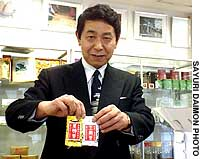 Kazuo Kodera, president of Kaito Brothers Co. in Shinjuku Ward, Tokyo, shows off two very expensive tea bags -- the 7-gram gold variety (left) sells for 200,000 yen, while the silver (right) goes for 100,000 yen.