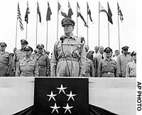 U.S. Army Gen. Douglas MacArthur reviews more than 15,000 troops of the Occupation from all over Japan at the Imperial Palace in Tokyo on July 4, 1949.