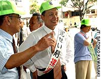 Hiroshi Yamada, mayor of Tokyo's Suginami Ward, talks with a ward official after participating in an antidrug campaign in front of JR Asagaya Station.