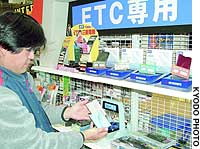 A customer views automatic highway toll-paying units at the Autobacs Tokyo Bay Shinonome outlet in Koto Ward.
