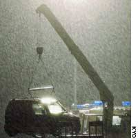 A crane lifts a minivehicle containing the bodies of three murder victims out of the Suwa River in Omuta, Fukuoka Prefecture, on Thursday night.