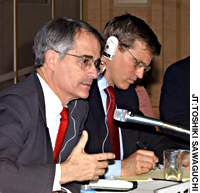 Bruce stokes addresses a symposium Wednesday in Tokyo, while copanelist Patrick Cronin listens.