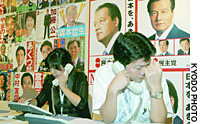 Staffers at the Democratic Party of Japan's election headquarters in Tokyo exchange information about the party's dismal showing Sunday evening.