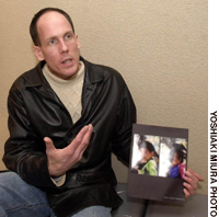 Canadian Murray Wood holds a photo of his two children, whom he has not seen since his Japanese ex-wife took them to Japan in November 2004, recently at a Tokyo hotel.