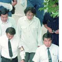 Tsutomu Miyazaki, escorted by Tokyo police, visits the scene of one of the murders he committed, in Koto Ward in June 1989.
