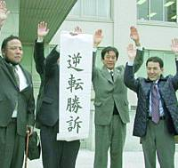 Yoshihiro Kano (left), of the National Association for the Rescue of Japanese Kidnapped by North Korea, gestures outside the Fukuoka High Court after it ruled Thursday that a local pro-North Korea organ's facility can be taxed.