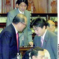 Disgraced Democratic Party of Japan lawmaker Hisayasu Nagata apologizes to Liberal Democratic Party Secretary General Tsutomu Takebe at the Diet on Thursday as Chief Cabinet Secretary Shinzo Abe looks on.