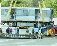 A train car on the Yurikamome Line that lost a wheel is loaded onto a trailer Saturday in Shinagawa Ward, Tokyo.