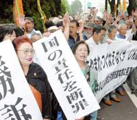 Plaintiffs and their supporters rejoice Friday outside the Tokyo District Court after winning compensation for pneumoconiosis, a disease many workers caught while working on state tunnel projects. | KYODO PHOTO