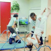 Instructors give somersault lessons at Sporty-One studio in Tokyo's Shibuya Ward earlier this month. | KYODO PHOTO