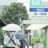 Commuters emerge from Kasumigaseki Station in Tokyo amid a downpour as Typhoon Maria approached the Kanto region Wednesday. | KYODO PHOTO