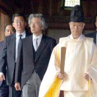 Prime Minister Junichiro Koizumi is led by a Shinto priest at Yasukuni Shrine after paying his respects at the main altar early Tuesday. | SATOKO KAWASAKI PHOTO