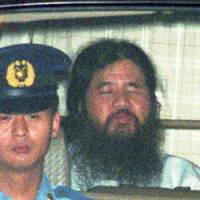 Shoko Asahara is driven from the Tokyo District Court to Metropolitan Police headquarters in July 1995. | AP PHOTOS