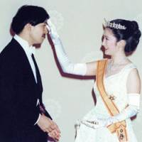 Princess Kiko fixes Prince Akishino's hair during their wedding photo shoot on June 29, 1990. | POOL PHOTO
