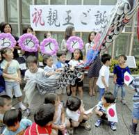 Children help put up a carp streamer to celebrate the birth of a boy to Princess Kiko on Sept. 6 in front of JR Mejiro Station in Tokyo. | KYODO PHOTO