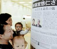 Women carrying babies look at a newspaper in Meitetsu Nagoya Station on Tuesday reporting the name chosen for the new prince. | KYODO PHOTO