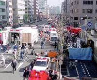 Rescue workers provide emergency care to subway passengers outside Tsukiji Station in Tokyo following the sarin gas attack by Aum Shinrikyo on March 20, 1995. | KYODO FILE PHOTOS