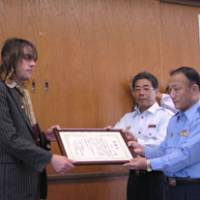 Simon Bartz, a writer and editor with The Japan Times, receives a certificate of appreciation Wednesday from Masaomi Hagio, head of the Kyoto Prefectural Police force's Shimogamo Station. | KYOTO CITY FIRE DEPARTMENT PHOTO