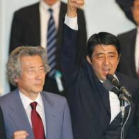 Shinzo Abe, accompanied by his predecessor, Junichiro Koizumi, raises a fist after winning the Liberal Democratic Party's presidential election on Sept. 20. | AP PHOTO