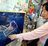 A protester on May 22 points to the spot on an aerial photo of Henoko, northern Okinawa Island, where two runways will be built for the relocation of the U.S. Marine Corps Air Station Futenma. | AP PHOTO