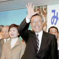 DPJ-suppported Yuhei Sato waves to supporters Sunday evening after securing a win in Fukushima Prefecture's gubernatorial election. | KYODO PHOTO