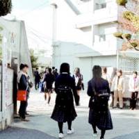 Students enter a junior high school in Tondabayashi, Osaka Prefecture, Monday morning, a day after a fellow student apparently committed suicide.