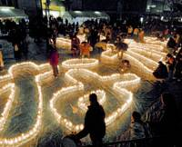 The word 'Nagata' is created with hundreds of candles during a memorial held Wednesday evening for victims of the 1995 Great Hanshin Earthquake at the city's Nagata Ward, which was among the hardest hit by the killer quake. | KYODO PHOTO