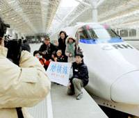 Travelers have their picture taken in front of a high-speed train modeled after JR East's Hayate bullet train Sunday. | KYODO PHOTO