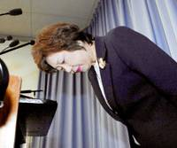 An apologetic Osaka Gov. Fusae Ota bows during a news conference Tuesday to announce the punishment of prefectural officials involved in a slush-fund scandal. | KYODO PHOTO