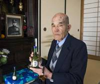 Itsuo Ashibe, younger brother of Petty Officer Mamoru Ashibe, who was aboard the Imperial Japanese Navy's midget submarine that raided Sydney Harbor in 1942, sits at home last December with a bottle of Mamoru's favorite sake in front of an altar dedicated to his brother. | ROBERT GILHOOLY PHOTO