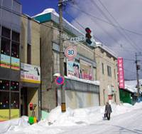 A lone shopper passes a closed store on the main street of Yubari, Hokkaido. The store bears nostalgic signboards of old movies to support the Yubari International Fantastic Film Festival, which was called off after the city went bust. | KANAKO TAKAHARA PHOTOS