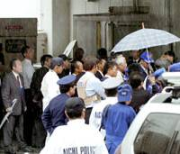 Police, bank employees and bystanders gather at the rear entrance of a Bank of Tokyo-Mitsubishi UFJ branch Tuesday while robbery suspect Junji Chatani, a Nara taxation official, holds a clerk hostage. | KYODO PHOTO