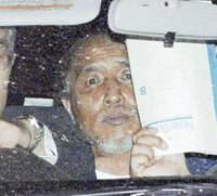 Hisato Obayashi is driven in a police vehicle to Aichi Police Station following his surrender Friday evening. ending a 29-hour standoff at his home in Nagakute, Aichi Prefecture. | KYODO PHOTO