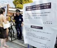 A security guard at Waseda University stops a young woman at the gate of the university in Tokyo on May 21. The notice posted at the gate explains that the university grounds will be closed from May 21 to 29 due to a measles outbreak. | KYODO PHOTO