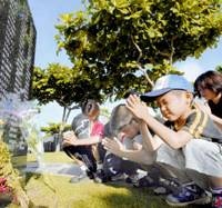 Children offer prayers in front of tablets bearing the names of people killed in the Battle of Okinawa at Peace Memorial Park in Itoman, Okinawa Prefecture, on Saturday, the 62nd anniversary of the end of the bloody fighting. | KYODO PHOTO