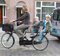 Femke De Vries, bicycling with her sons, Bink, 2, and Vosse, 5, in Haarlem, Netherlands, works a three-day, 25-hour week and spends the rest of her time at home. | SETSUKO KAMIYA PHOTO
