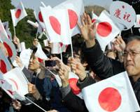 Well-wishers wave Hinomaru flags during a public appearance by Emperor Akihito on his 73rd birthday last December at the Imperial Palace. | AP PHOTO