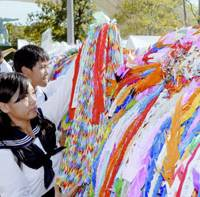 High school students hang strings of paper cranes Thursday in Nagasaki's Peace Park to pray for peace on the 62nd anniversary of the atomic bombing of the city. | KYODO PHOTOS