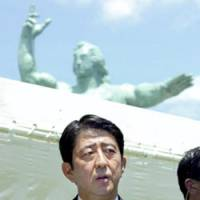 Prime Minister Shinzo Abe speaks to reporters at Nagasaki's Peace Park on Thursday, the 62nd anniversary of the atomic bombing. | POOL PHOTO