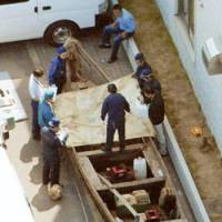 Police on June 2 inspect a small wooden boat that carried a family of four North Korean defectors to this coastal town on the Sea of Japan. | KYODO PHOTO