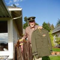 Lee Olson shows off his olive drab uniform, with navy wings, and wartime leather flight jacket at a friend's house last month in Maple Valley, Wash. | ERIC L. DUE PHOTO
