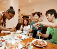 Young singles share food and tipple at Social Apartment Yomiuriland in Aso Ward, Kawasaki. Some tenants are non-Japanese. | KYODO PHOTO