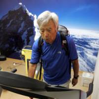 Yuichiro Miura carries weights on his back as he walks a treadmill against a photo panel of Mount Everest in a low-oxygen room at his home in Tokyo in June. | AP PHOTO