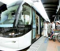Passengers board a two-car Portram light rail tram in the city of Toyama last month. | KYODO PHOTO